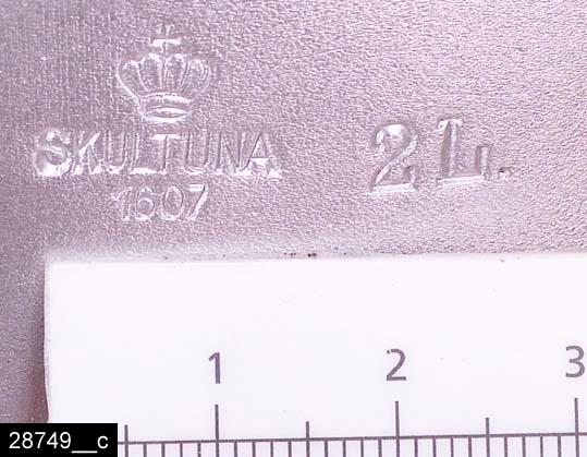 """Anmärkningar: Tvillinggryta, 1940-tal.  Halvmåneformade grytor som är tillverkade för att sitta ihop med varandra (bild 28749__a-b). Vardera gryta har dubbla handtag samt ett handtagsförsett lock. På det ena handtaget hänger en lapp med texten """"SKULTUNA BRUK GRUNDLAGT ÅR 1607"""". Till höger om det ena handtaget finns stämplar i form av en krona samt texten """"SKULTUNA 1607 2L"""" (bild 28749__c). I den ena grytan finns en lapp med skötselråd för grytan (bild 28749__d). Grytorna är avbildade i kataloger från Skultuna från 1940-talet (bild 28749__e). Enligt en broschyr, utgiven av museet 2007 och benämnd """"Skultunastämplar 1800-2000"""", började den typ av stämpel som finns på föremålet användas 1922. Den användes fortfarande år 2007. H:145 Br:245 L:385  Tillstånd: Nyskick.  Historik: Gåva från SAPA AB, Division Service, 2002. Föremålet stod i ett skyddsrum på bruksområdet i Skultuna."""