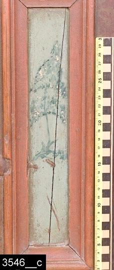 Anmärkningar: Hörnskåp, omkring 1800.  Framskjutande avfasat krön. Spegelförsedd enkeldörr med gerade och profilerade lister. I spegeln finns ett blomstermåleri mot grön botten. På dörren finns också en konturformad nyckelskylt i järn (bild 3546__b). På sidorna finns dubbla rektangulära nedbottningar med gerade och profilerade lister. I dessa finns ett blomstermåleri erinrandes om japanska träd (bild 3546__c). Baktill finns en upphängningsanordning i järn. Profilerade och kälade sockellister. H:950 Br:790 Dj:490  Tillstånd: Skåpet är låst och går ej att öppna, nyckel saknas. Vänster sockellist saknas. Baksidan lagad på två ställen med plåtbitar.  Historik: Från Per Ersson, Sörgården, Ullvi, Munktorp sn. Inköpt från Jan Ersson Ullvi, Munktorp sn, för 10:-, 24/7 1925.  Negativnummer A 1455, X-1595