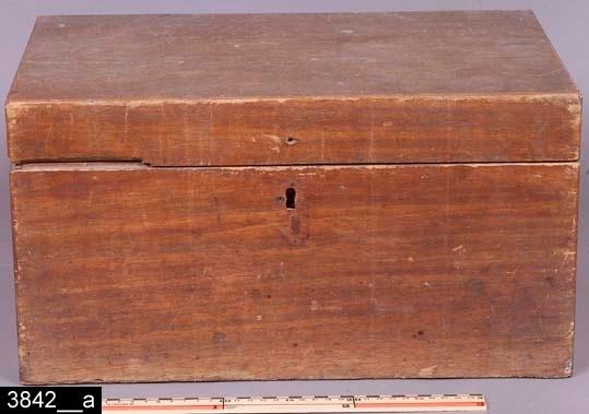 Anmärkningar: Skrin, 1800-tal.  Gångjärnsförsett platt lock. Invändigt är skrinet tomt (bild 3842__b). Hela skrinet är av mahogny utom bottenstycket som är av furu. H:235 Br:435 Dj:285  Tillstånd: Nyckel och nyckelskylt saknas. Skada på vänstra sidan av fronten.  Historik: Inköpt på häradshövding T. Kaléns auktion genom Ida Nygren för 1,5 kronor, 1925.  Negativnummer: X-87