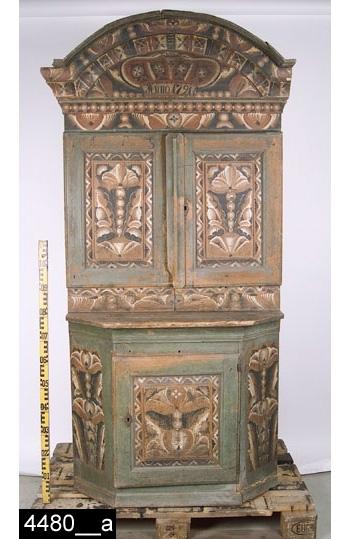 Anmärkningar: Skänkskåp, grönt i ett stycke med kurbitsmålning, målad datering 1791, s.k. kronskåp, benämning efter den målade kronan i krönet (bild 4480__b).  Framskjutande rundat krön. Spegelförsedda pardörrar med falsk avfasad gering. Två draglådor. Skänk med framskjutande skänkskiva. Enkeldörr med falsk avfasad gering. Överdel med skedhylla och ett hyllplan invändigt. Skänkdel med ett hyllplan invändigt. På insidan av dörren finns en anordning trol. avsedd för skedar (bild 4480__e). H:2020 Br:1010 Dj:600  Färgen på dörrarna bär spår av naturligt slitage.  Skåpet är snickrat i Dalarna, skåpstypen är karaktäristisk för detta landskap. Måleriet är utfört av en dalmålare. Dalskåp med kurbitsmålning är kända långt utanför Dalarnas trakter. De har framför allt spridits till Gästrikland, Hälsingland, Uppland och Västmanland. Troligen har de sålts på marknader, både målade och omålade. Möjligen har dalfolket även sålt dem direkt i respektive landskap. Dalfolkets arbetsvandringar är väl belagda inom forskningen. Man vet också att dalmålarna kunde röra sig på mycket stora ytor, t.o.m. till Norge och Finland. Att de tog sig ned till Västmanland råder det ingen tvekan om.  Tillstånd: Krönlist saknas på båda sidor (bild 4480__c,d,f). Lås saknas på skänkdelens dörr. Sockellist saknas på båda sidor.  Historik: På överskåpets vänstra dörrs övre ram är A P S Målat i svart, Enligt liggaren står detta för Anders Persson som var farfars far till Christina Andersdotter. Köpt 1925-08-28 för 40:-, från Gustaf Andersson och Christina Andersdotter, Häljesta, Munktorp sn.  Negativnummer A-1599, X-1596