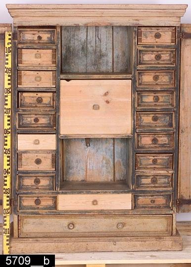 Anmärkningar: Kryddskåp, gulmålat, 1700-talets senare hälft.  Framskjutande och profilerat krön. Pardörrar med dubbla speglar omgivna av gerade och profilerade lister. Den högra dörren har en nyckelskylt i järn. Färgen längst upp på den högra dörren bär spår av naturligt slitage. Draglåda med två svarvade träknoppar. Invändigt tjugo lådor i varierande storlek (bild 5709__b). Femton lådor har svarvade träknoppar, fem har skurna träknoppar. Invändigt en hanki järn på vänster dörr samt tillhörande hankfäste i järn på ett av hyllplanen (bild 5709__b). Profilerade sockellister nederst. H:1230 Br:900 Dj:385  Tillstånd: Tre lådor senare. Lister saknas på flera av lådornas fronter. Fem lådor har senare träknoppar. Lås saknas. Lådorna doftar gammal krydda.  Historik: Köpt 1927 av fru Ida Nygren, Västerås. Ursprungligen från Irsta sn.  Negativnummer X-1678
