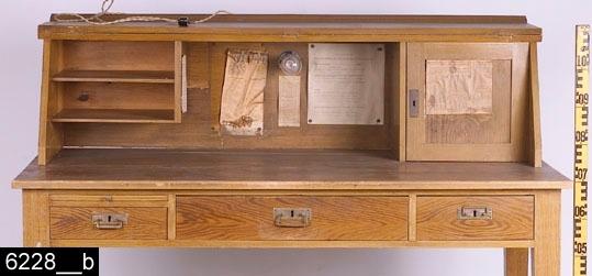 """Anmärkningar: Expeditionsskrivbord, jugend, omkring 1900.  Låsbar och gångjärnsförsedd uppsatsdel med snedklaff och nyckelskylt i mässing, uppsatsdelen är itappad i skrivbordet. Snedklaffen går att fälla upp (bild 6228__b). Invändigt finns en låsbar lucka med mässinsnyckelskylt. Invändigt finns ett hyllplan (bild 6228__c). Invändigt i uppsatsdelen finns vidare sex stycken pappersnotiser från 1920-talet (en del av dem är försedda med årtal) som bl.a. anger tågtider (bild 6228__d-i) samt en glödlampa med tillhörande sladd. En lapp anger att Fornminnesföreningens öppettider var söndagar kl 1-3 (bild 6228__i). I framsargen finns tre draglådor med mässingshandtag i stilen jugend (bild 6228__j). Draglådorna är i botten märkta """"7K"""" (7:e kompaniet), en av dem är dessutom märkt """"Kungl Västmanlands Regemente 7. komp"""" (bild 6228__k). Ovanför den vänstra draglådan finns ett utdrag med dragknopp i mässing (bild 6228__c). Fyra nedåt avsmalnande ben. H:1115 Br:840 L:1415  Hela möbeln är ådringsmålad, måleriet imiterar ek.  Tillstånd: Nycklar till låsen saknas. Möjligen är fötterna något kortade. Rester av förgyllning finns på mässingshandtagen (bild 6228__k).  Historik: Gåva av Kungliga Västmanlands Regemente 1928."""