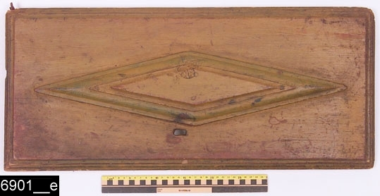 Anmärkningar: Hörnskåp, gulmålat, 1700-tal.  Svagt framskjutande krön. Profilerad inskjuten list under krönet. Enkeldörr med barockformad romboid förkroppning. Invändigt två hyllplan samt anordning för skedar längst upp på innerdörren. Dörren flankeras av nedbottningar som består av vardera två avlånga inlägg och tre mindre fyrkantiga inlägg. Till vänster respektive till höger om dessa nedbottningar finns ytterligare dubbla rektangulära nedbottningar med gerade och profilerade lister. Baktill finns en konturerad upphängningsanordning i järn (bild 6901__d). Profilerade sockellister. H:930 Br:585 Dj:390  Tillstånd: Vänster krönlist saknas. Dörren är lös och kan inte fästas i skåpet (bild 6901__e). Nyckelskylt, lås och nyckel saknas. Gammal lagning i järn längst ned till höger om dörren (bild 6901__c). Mittersta sockellisten saknas. Den gula färgen är gammal, men ej original. De ursprungliga färgerna har varit röd och blågrön (bild 6901__b).  Historik: Från Hubbo sn, inköpt på auktion 1928.  Negativnummer X-1601