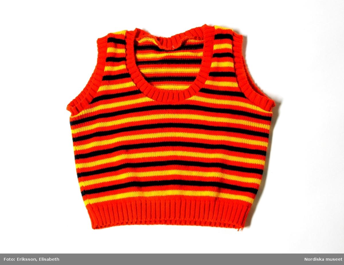 Slipover för kvinna av acryl. Tillverkad 1971. Använd av Lisbeth Holmström.  Midjekort med vid halsringning, tvärrandig i orangrött, mörblått och gult med röda ribstickade kantningar.