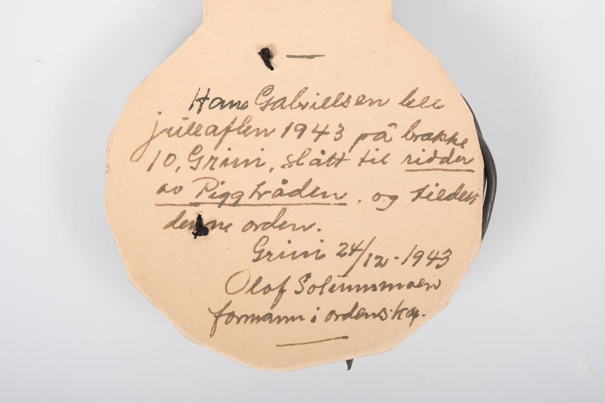"""Håndlaget orden laget i kartong og piggtråd på Grini. Kraftig kartong pæreformet tilskjært og med norske farger øverst, og kongeblå kant nederst. Sydd fast på nederdelen en """"G"""" i piggtråd med papirhyssing til å henge rundt halsen.  Håndskrevne initialer """"H.G."""" øverst på baksiden.   Håndskreven tekst nederst på baksiden av orden: """"Hans Gabrielsen ble julaften 1943 på brakke 10, Grini, slått til ridder av Piggtråden, og tildelt denne orden. Grini 24712-1943 Olaf Solumsmoen formann i ordenskap.""""  Tildelt Hans Gabrielsen slått til """"ridder av Piggtråden"""" den 24.12.1943."""