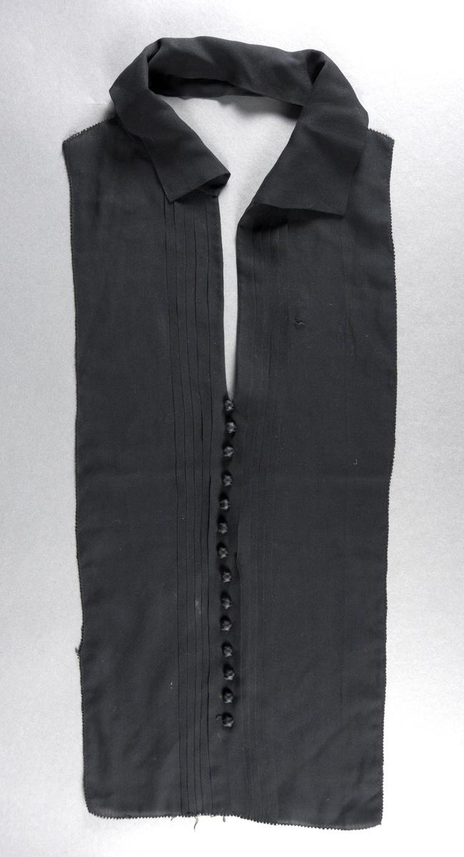 Et skjortebryst med krage laget av svart chiffon. I front er det et plissert parti med fem folder på hver side. Under utringningen er det sydd på en rad med 14 knapper trukket med svart stoff. Plagget har dyp utringning og en krage som står opp (sydd av dobbelt lag chiffon).