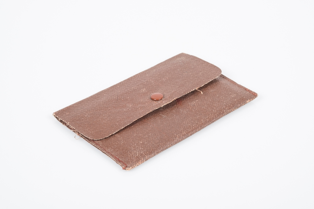 """Brun flat pung i """"kunstskinn"""", stoff med belegg og trykknapp. Inni en svart minnebok i kunstskinn, linjert papir med """"autografer fra krigsfanger""""."""