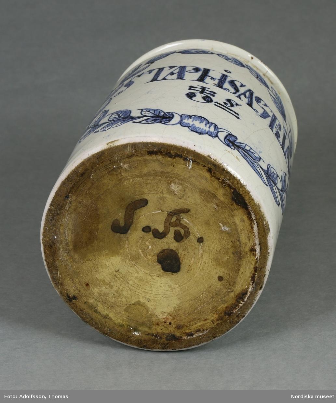"""Huvudliggaren:  """"LXVI a-c. 3 ståndkärl av fajans, vita m. blå ornering. a.chamomille b.  c. 2 med trälock, 1 utan""""."""