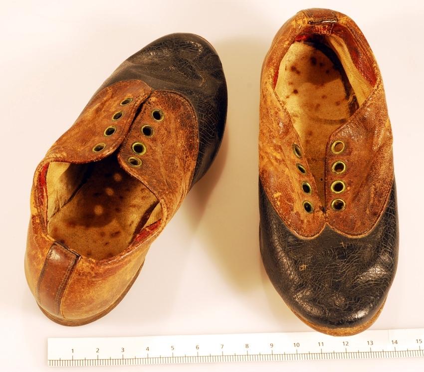 Anmärkningar: Ett par barnskor av svart och brunt läder. Lädret brunt vid hålen för snörning uppe på barnskon. Fyra öglor för att iträda skosnöre på var sida. Skosnören saknas. Liten klack. Inuti är skorna klädda med ljust tyg. Passar troligtvis ett barn runt ca 2 års ålder.