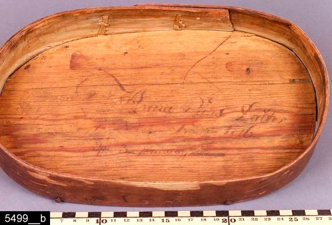 """Anmärkningar: Svepask, daterad 1816.  Oval svepask med lock. Ovansidan av locket är försett med ett blomstermåleri. På insidan av locket återfinns påskriften """"Anna Pärs Dotter / i Nibble Svedvi 1816 / den 3 januari"""" (bild 5499__b). Påskriften är delvis bortnött (den ovan angivna texten är hämtad från liggaren). Hela asken är brunmålad och bär spår av naturligt slitage. H:100 L:275 Dj:155  Tillstånd: Lock saknas.  Historik: Gåva från fru Pettersson, Kolbäcks sn, St. Åby, maj 1927."""