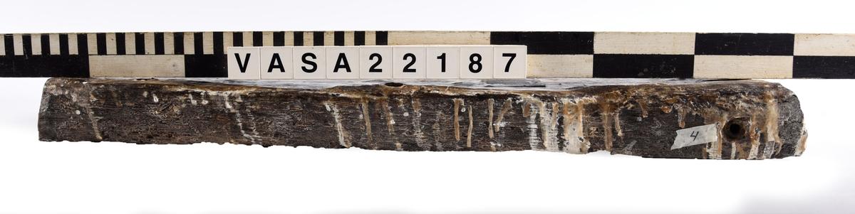 Tröskel till kanonport 24. Paralellogramformad, med fasade kanter och ändar. Väl bevarade ändor. 4 moderna genomgår spikhål, och 2 klart original spikhål. Vittrade ytor, med fläckor PEG.  Jarn impregnering och sprickning på ytan med mindre PEG.