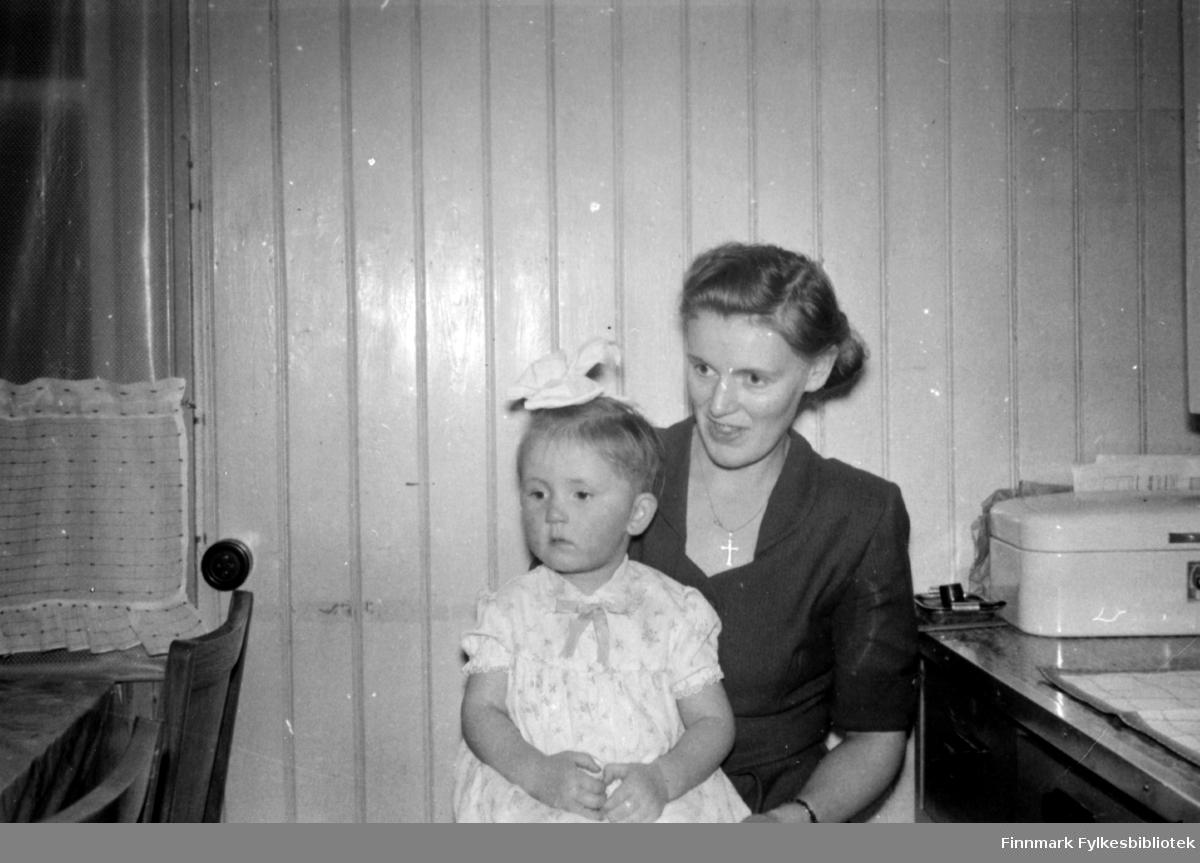 Solveig og mor. Fotografert på kjøkkenet. Spisebord til venstre, kjøkkenbenk til høyre. En brødboks i emalje til høyre på benken. Veggen er malt panel. Solveig er pyntet med hårsløyfe og kjole. Mor i kjole og smykke i halsen.  Familiealbum tilhørende familien Klemetsen. Utlånt av Trygve Klemetsen. Periode: 1930-1960.