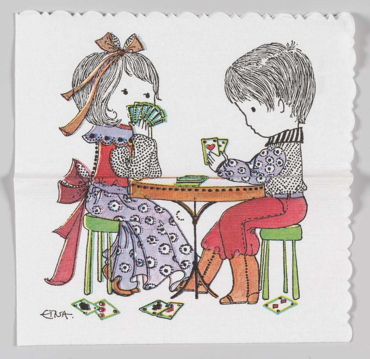 En gutt og en jente spiller kort ved et rundt bord.