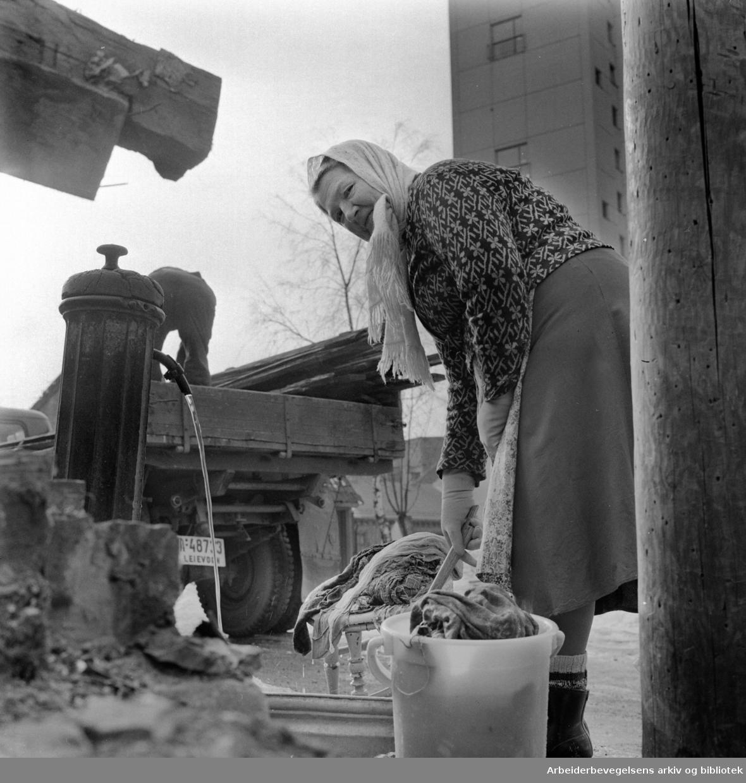 Enerhaugen. Langleiken. Olga Johansen ved vannposten..Mars 1963