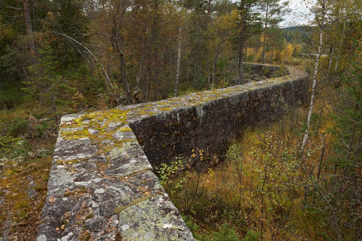"""Gråsteinsmurt, men sementfuget damarm ved utløpet av Nedre Bjørvatn eller Nedre Bjorvatn [navneform brukt i dokumenter fram til midten av 1900-tallet] i Tinn i Øst-Telemark.  Nedre Bjørvassdam ligger høyt oppe i den fløtbare delen av Rauavassdraget.  Damarmen er meget presist bygd, antakelig av tuktet stein.  På det stedet der dette fotografiet er tatt later den til å være en drøy meter bred og tilsvarende høy.  Damarmen føyer seg etter en bergrygg langs den myra som skulle være vannreservoar.  Muren går i rett linje noen meter, fortsetter deretter i en litt annen vinkel noen meter, for igjen å skifte retning på nytt.  Murkrona er så plan at den er behagelig å gå på.  Her kunne det sikkert også kjøres trillebår, om det var behov for det.  Der hvor dette fotografiet er tatt går den gjennom et myrlandskap hvor det har vokst fram en del krattskog etter at bruken av dammen opphørte.  Da fløtinga pågikk ble slik vegetasjon holdt nede, slik at den ikke skulle være i vegen for arbeidet.  Myrer var for øvrig populære oppdemmingsobjekter der hvor det skulle magasineres mye fløtingsvann, for det flate myrterrenget gav rom for store vannvolumer uten at dammene behøvde å bli så djupe.  Til gjengjeld måtte det bygges lange damarmer i slikt flatt terreng, noe dette fotografiet illustrerer.   Fløtinga i Rauavassdraget begynte gjerne i midten av mai og pågikk tre-fire uker.  Deretter ble tømmeret fra vassdragets nedslagsfelt buksert mot Tinnoset med slepebåten """"Maar"""".  Utover i 1960-åra krympet fløtinga i sidevassdragene noe, for det ble stadig vanskeligere å rekruttere folk til sesongarbeid langs vassdragene samtidig som mulighetene for lastebiltransport av tømmer ble stadig bedre.  I Rauavassdraget oppsto det i tillegg spesielle problemer knyttet til slitasje på betongforblendinga i Rauatunnelen, nederst i vassdraget.  1968 var det siste året det var fløting her."""