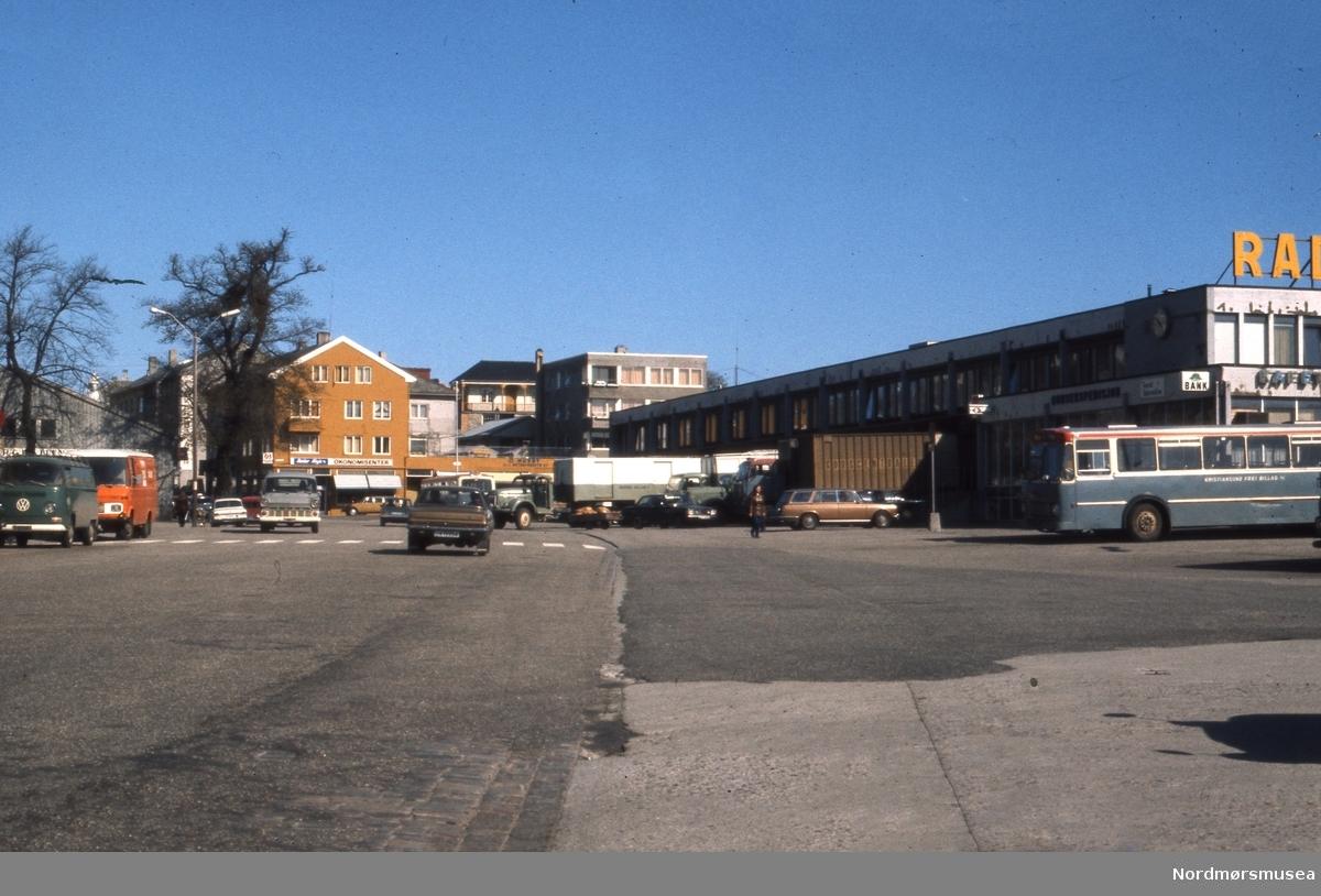 Rutebilstasjonen på Kirkelandet i Kristiansund. Fotografering  er nok tidligst 1970. Bussen til høyre, i fargene til Kristiansund Frei Billag, er tidligst en 1970-modell.  (Info: Sveinung Berild). fra ei samling Fotografier og karttegninger, fotografert eller samlet av Arkitekt MNAL Kristian Sylthe (f. 18.06.1926) ved Kristiansund kommune i sitt virke som kommunearkitekt (senere næringssjef) samt som sekretær i Oljeutvalget fra begynnelsen tidlig 1970. Samlingen kan i hovedsak dateres mellom 1945 til 1980. Samlingen er gitt i gave av Kristiansund kommune. Fra Nordmøre museums fotosamlinger.