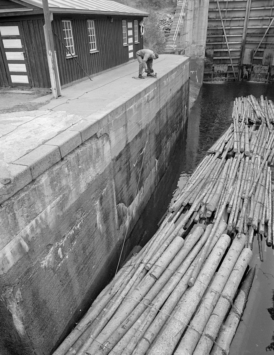 Pensjonert slusemester Odd Johansen (1917-1993) fortøyer ei såkalt slusevending med tømmer i en bolt på kanten av plattformen ved et av slusekamrene. Han brukte en vaier med endekrok, som ble hektet på et av vaierbindene på den fremste tømmerbunten i slusekammeret. Fortøyingsvaieren kom egentlig fra et nokkespill ved sluseporten (jfr. SJF-F.009389), og den skulle seinere, når slusekammeret var nedtappet, brukes til å trekke tømmeret over i neste kammer (jfr. SJF-F.009390).  På plattformen bak fortøyingspunktet ser vi Haldenvassdragets Kanalselskaps verkstedbygning på Brekke.  Johansen var arbeidskledd, med beavernylondress utenpå ei kvit skjorte og med alpelue på hodet.  I sitt yrkesaktive liv hadde han i hovedsak hatt Strømsfoss sluse som arbeidsplass, men som pensjonist var han det siste fløtingsåret i Haldenvassdraget (1982) med og hjalp til i ulike deler av vassdraget.  Dette er det tredje sluseanlegget som ble bygd ved Brekke.  Det første, som den kjente vassdragstekniske pioneren Engebret Soot (1786-1859) hadde idéen til, ble bygd i slutten av 1850-åra av stedlig stein med rosentorv som tettingsmateriale i murverket.  Dette sluseanlegget ble ødelagt under flom alt i 1861.  I perioden 1873-1877 bygde det statlige Kanalvesenet et nytt sluseanlegg ved Brekke, også dette med fire slusekamre, men åpenbart mer solid enn det første.  Fredrikshald (Halden) kommune sikret seg fallrettigheter ved Brekke alt i 1904.  Det varte imidlertid helt til 1918 før kraftutbyggingsprosjektet her ble påbegynt.  I åra som fulgte ble det bygd en massiv betongdam ved Brekkefossen som var 110 meter lang, og som på grunn av vanskelige grunnforhold måtte få en høyde på opptil 38 meter.  Kraftverksdammen hevet med andre ord vannspeilet i den ovenforliggende delen av Stenselva kraftig, slik at det ble nødvendig å bygge et helt nytt sluseanlegg.  Dette ble altså utført i armert betong, med stålporter og hydraulisk styring.  En liten historikk om tømmerfløting og kanaliseringsarbeid i Haldenv