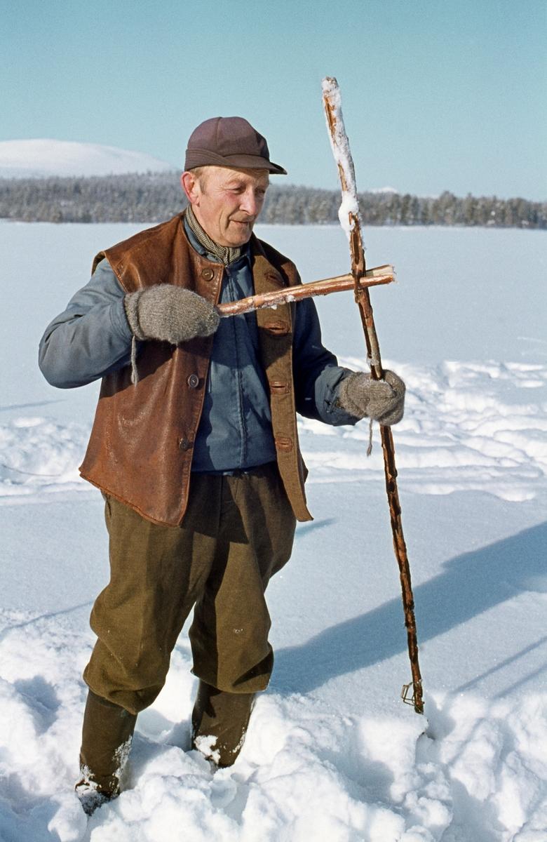 Osvald Kolbu viser utstyr for støkrokfangst av lake med fiskesaks på innsjøen Isteren i Engerdal i Hedmark.  Saksa besto av to metallkroker som var hengslet sammen med ei nagle og utstyrt med ei spiralfjær.  Agnfisken festes på den ene kroken.  Deretter spente fiskeren fjæra og gildret sakseleddene.  Nå fisken forsynte seg av agnet, klappet krokene sammen slik at den ble sittende fast.  Slike fiskesakser ble masseproduserte, og oftest brukt til gjeddefangst, men her altså på lake.  Kolbu var kledd i lysebrune vadmelsbukser, dongerijakke og skinnvest.  På hendene hadde han ullvotter og på hodet ei skyggelue.  Bildet ble tatt i slutten av februar 1977.