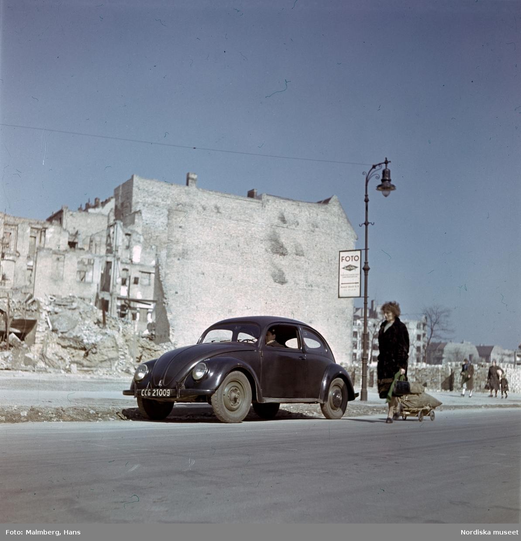 Berlin. På en gata sitter soldat ur de brittiska ockupationstrupperna i en Volkswagen, bredvid drar en kvinna på en kärra.