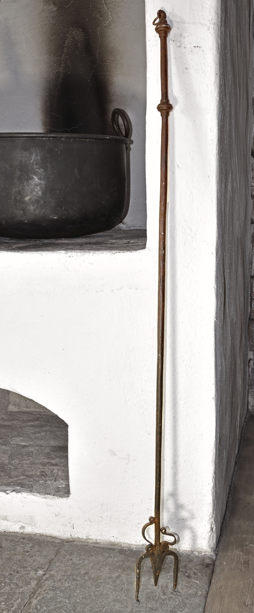 Eldgaffel av rund järnten med två klor, Ovanför klorna två dekorativa band av järn. Rundad handtagsdel mellan två profilerade knoppar, avlutad med flat del med genomträdd järnnring.