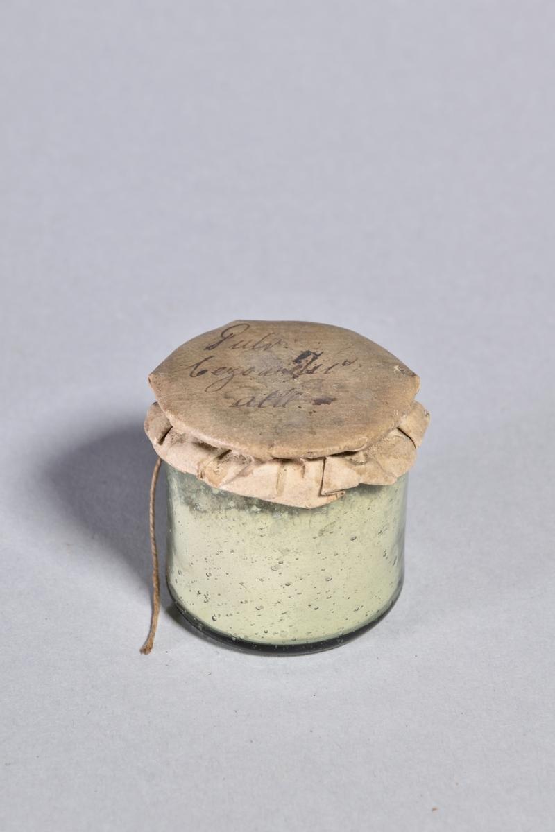 Burk av gröntonat glas, cylindrisk med överbundet lock av papper, fäst med tunt snöre. Innehåller ljust pulver.