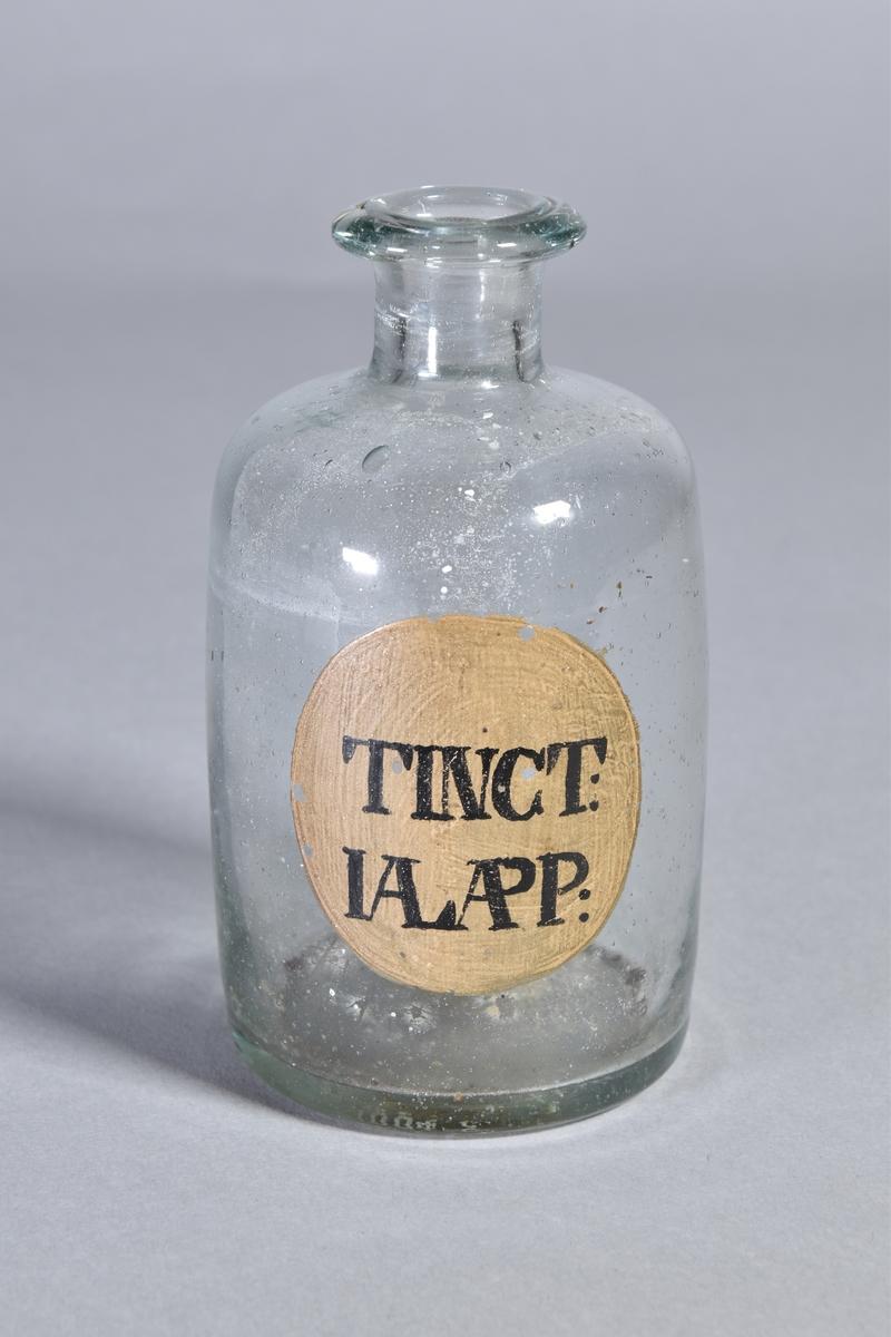 Flaska av klart glas, cylindrisk, kort hals med utsvängd mynning. Påmålad etikett med svart text. Rester av innehåll.