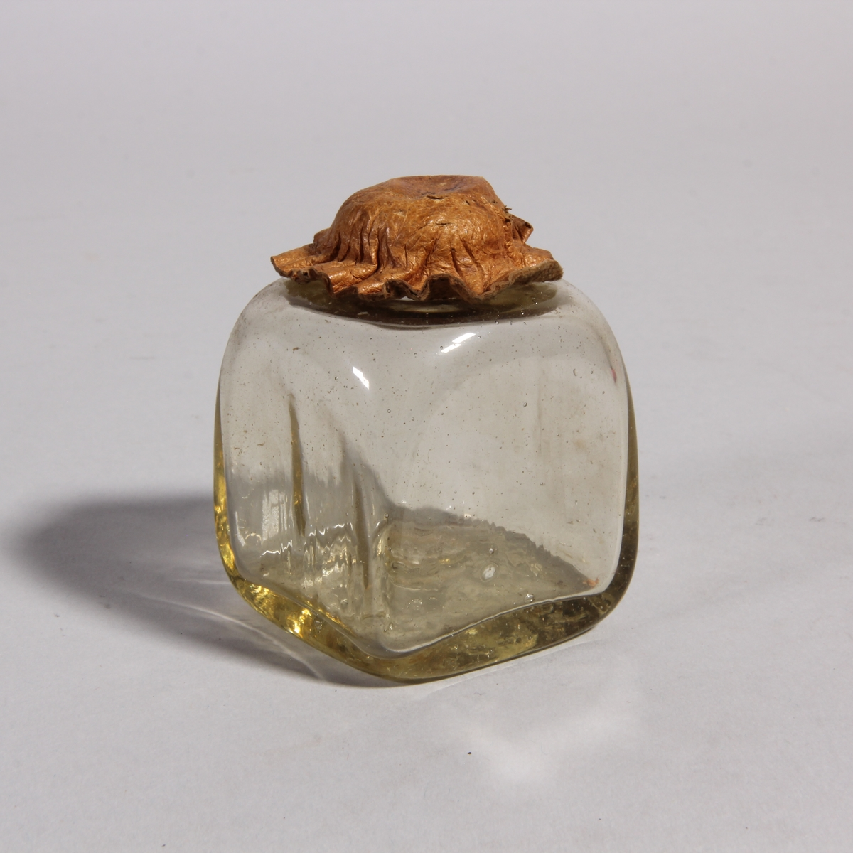 Husapotek bestående av låda med fällock och invändig fackinredning. Handtag av mässing på locket. Omålad. I lockets insida utfällbar skiva. På skivan klistad pappersetikett med förklaring till viktsatserna. På framsidan två mindre lådor bakom fällbar front. Lådan innehåller 7 fyrkantiga större gultonade glasflaskor med skinnförslutning, 6 kvadratiska mindre gultonade glasflakor och burkar, varav 4 st med skinnförslutning, 4 smala fyrkantiga flaskor av gultonat glas. Översta lådan innehåller 3 rivjärn av metall, 1 spatel med sked av metall. Nedersta lådan innehåller balansvåg av mässing med vikter. Nyckel.