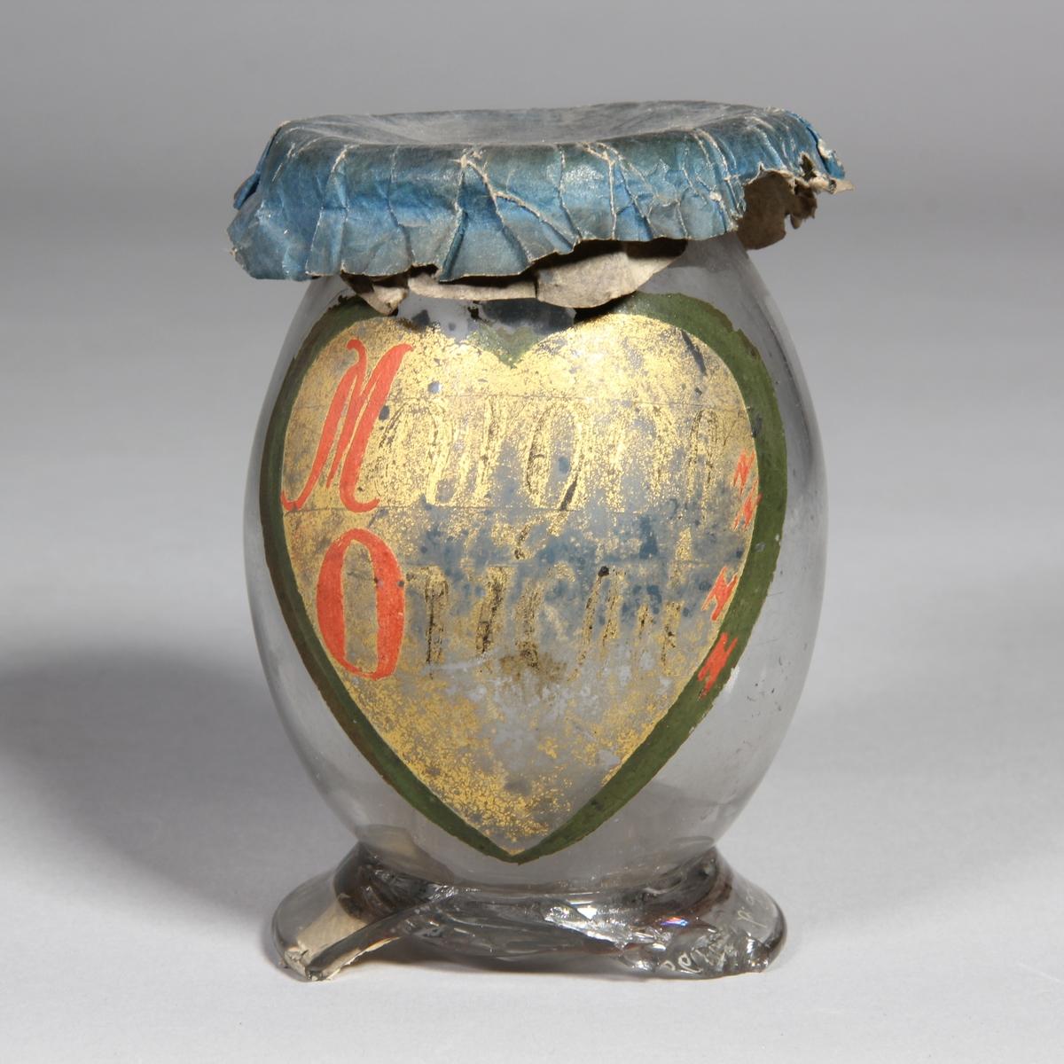 Burk av klart glas. Rundad med utvikt fot, överbundet lock av papper. Två målade etiketter, den ena hjärtformad med text och den andra utan text.