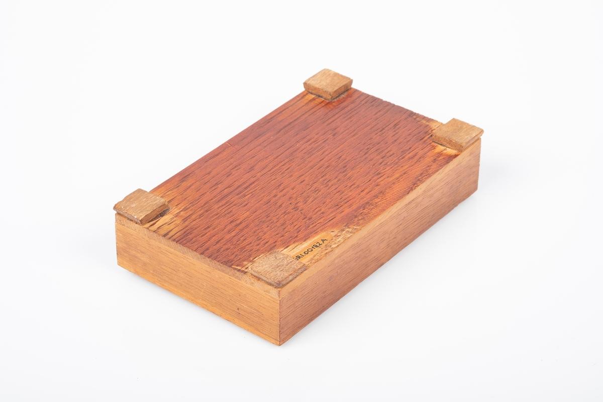 Skrin laget av tre. Skrinet har fire kvadratiske ben og er lakkert. Påskrift på innsiden av skrinet.