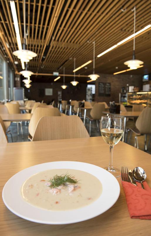Tallerken med fiskesuppe og glass med hvitvin på bord Kafeen i bakgrunnen.