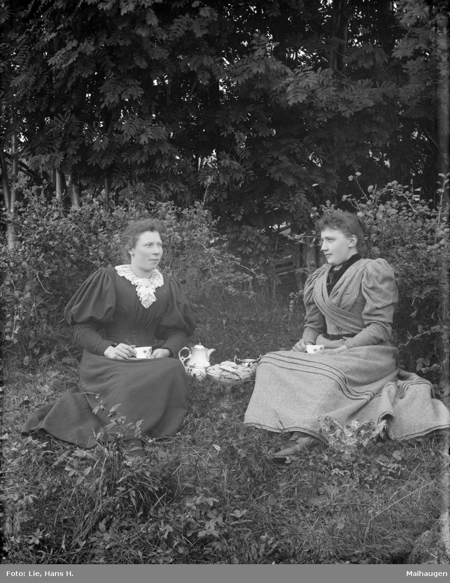 Gruppebilde, Anette Bryhn og Ingebjørg sitter på gressbakken.