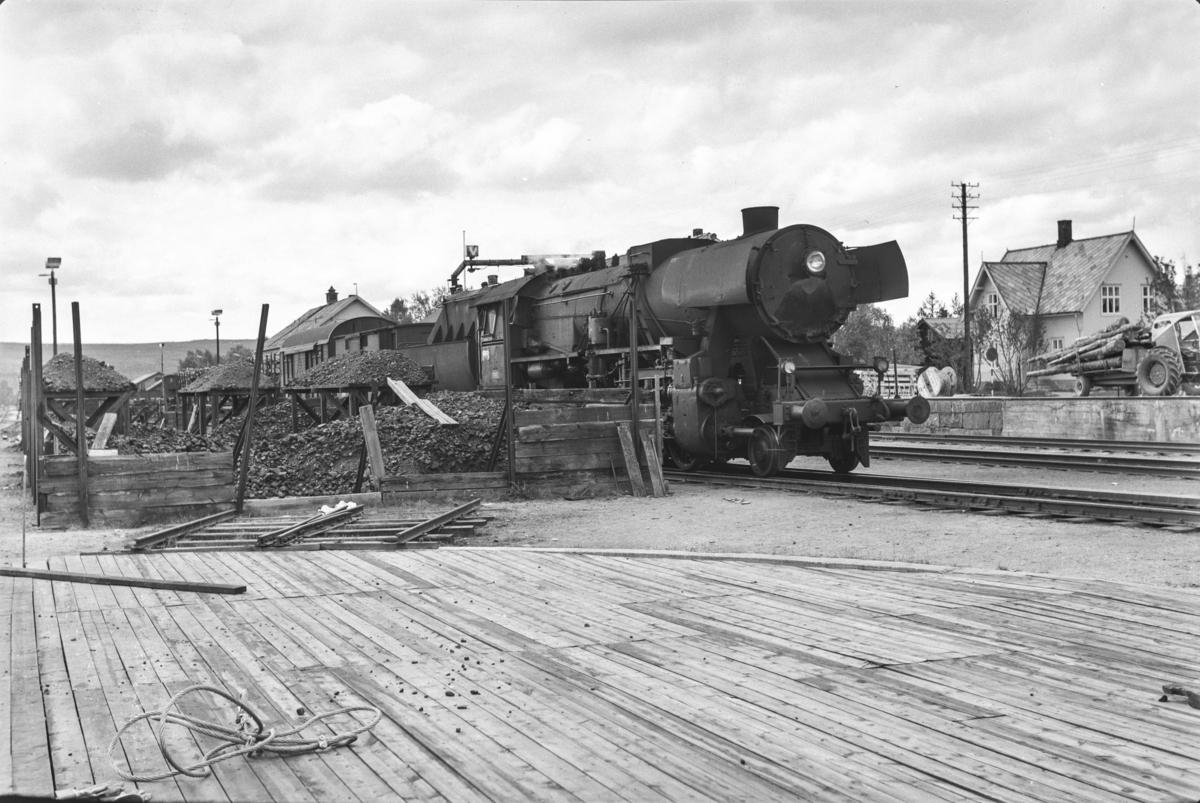 Vannfylling fra vannstender på damplokomotiv type 63a nr. 5860 på Røros stasjon. Lokomotivet benyttes i underveisgodstoget fra Trondheim til Hamar over Røros, tog 5712.