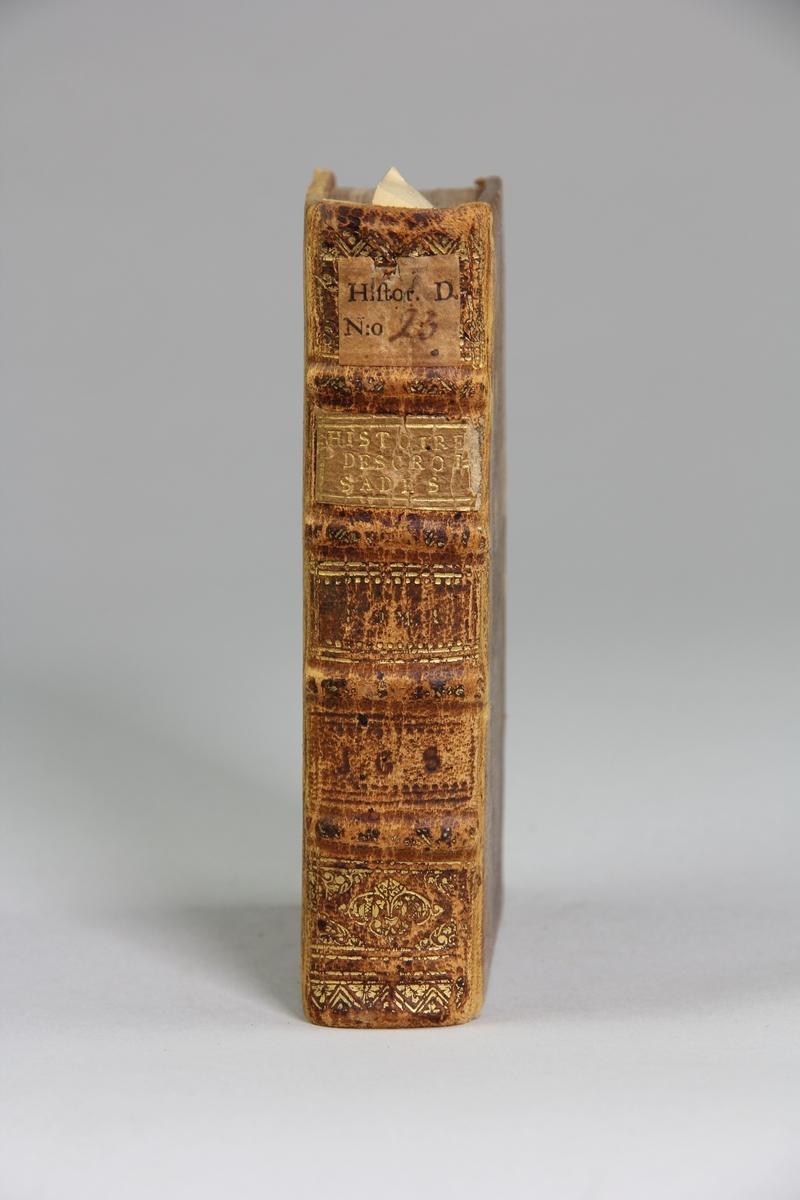 """Bok, helfranskt band, """"Histoire des croisades pour la delivrance de la terre sainte"""", del 1, skriven av Louis Maimbourg, utgiven i Paris hos Sebastien Mabre-Cramoisy 1731. Skinnband med blindpressad och guldornerad rygg i fyra upphöjda bind, titelfält med blindpressad titel , fält med volymens nummer, ett fält med ägarens initialer samt påklistrad pappersetikett. Med rödstänkt snitt."""