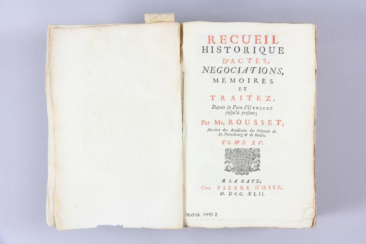 """Bok, pappband, """"Recueil historique d´actes, negotiations... depuis la paix d´Utrecht"""", del 15, tryckt 1742 i Haag. Marmorerade pärmar av papper, blekt rygg med etiketter med bokens titel, närmast utplånad, och samlingsnummer. Oskuret snitt, ej uppskuren."""