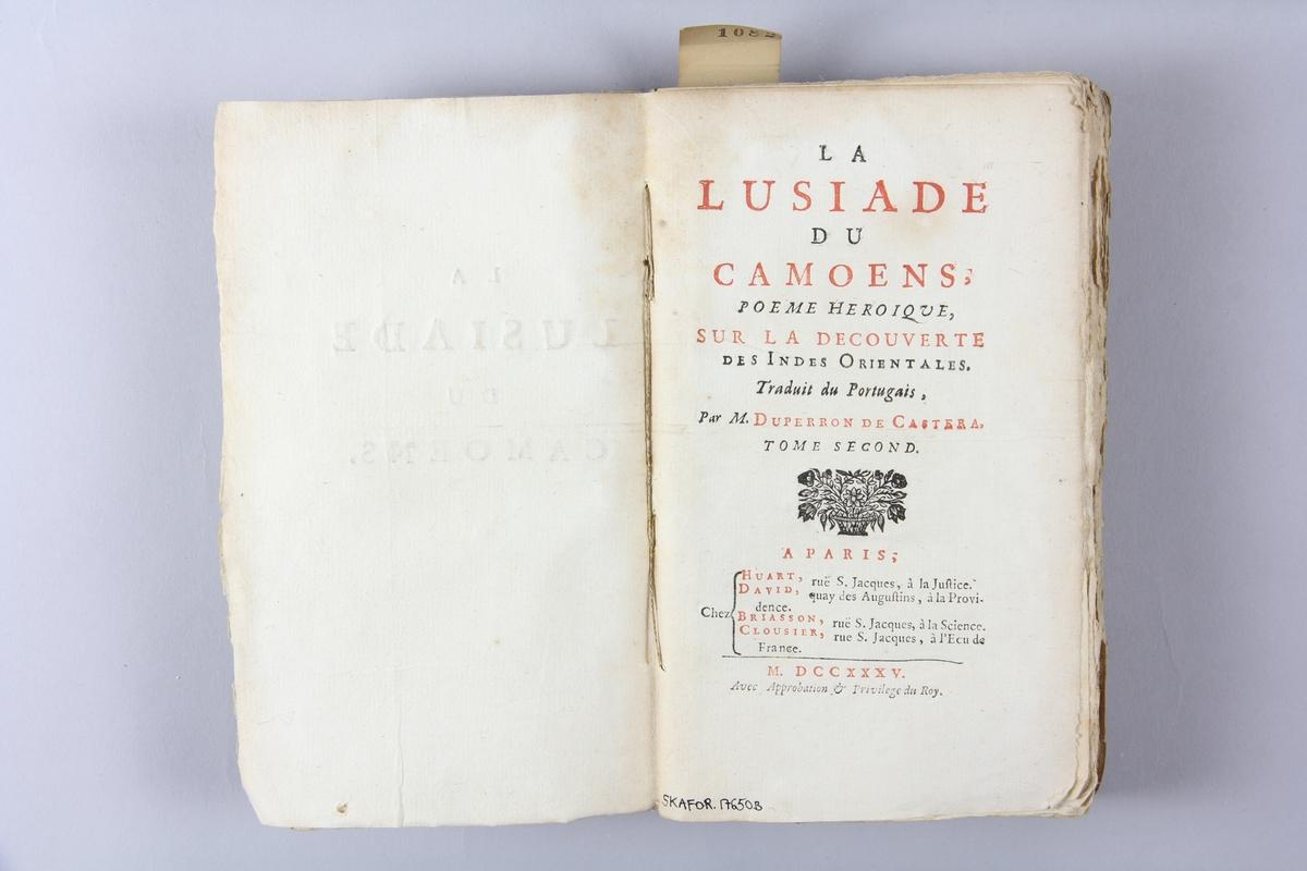 """Bok, häftad, """"La Lusiade de Camoens"""", del 2, tryckt 1735 i Paris. Pärm av marmorerat papper, oskuret snitt.  Blekt rygg med  pappersetikett med volymens titel och samlingsnummer. Illustrationer i koppartryck."""