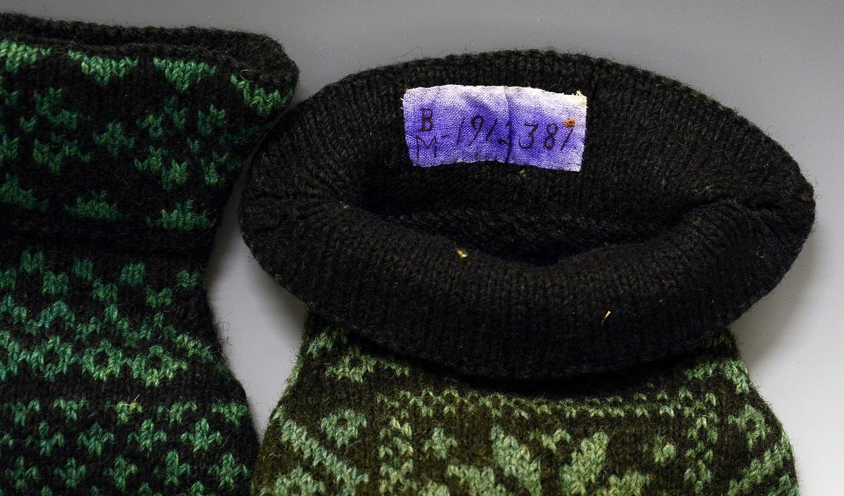 Herrevanter. Et par stikkede vanter i sort og grønt ullgarn. Vantene har en 8-bladsrose i midten foran, og seks 8-bladsroser plassert på kragekanten.