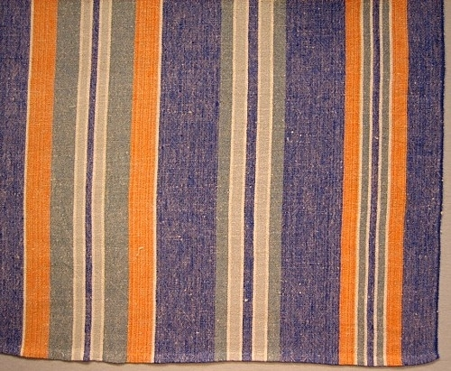Långrandig duk, såldes som metervara. Varp: cottolin i blått, grått, orange och vitt.Inslag: oblekttowgarnVävnota Inv.nr 1037:2-3, Skiss Inv.nr 1129:1