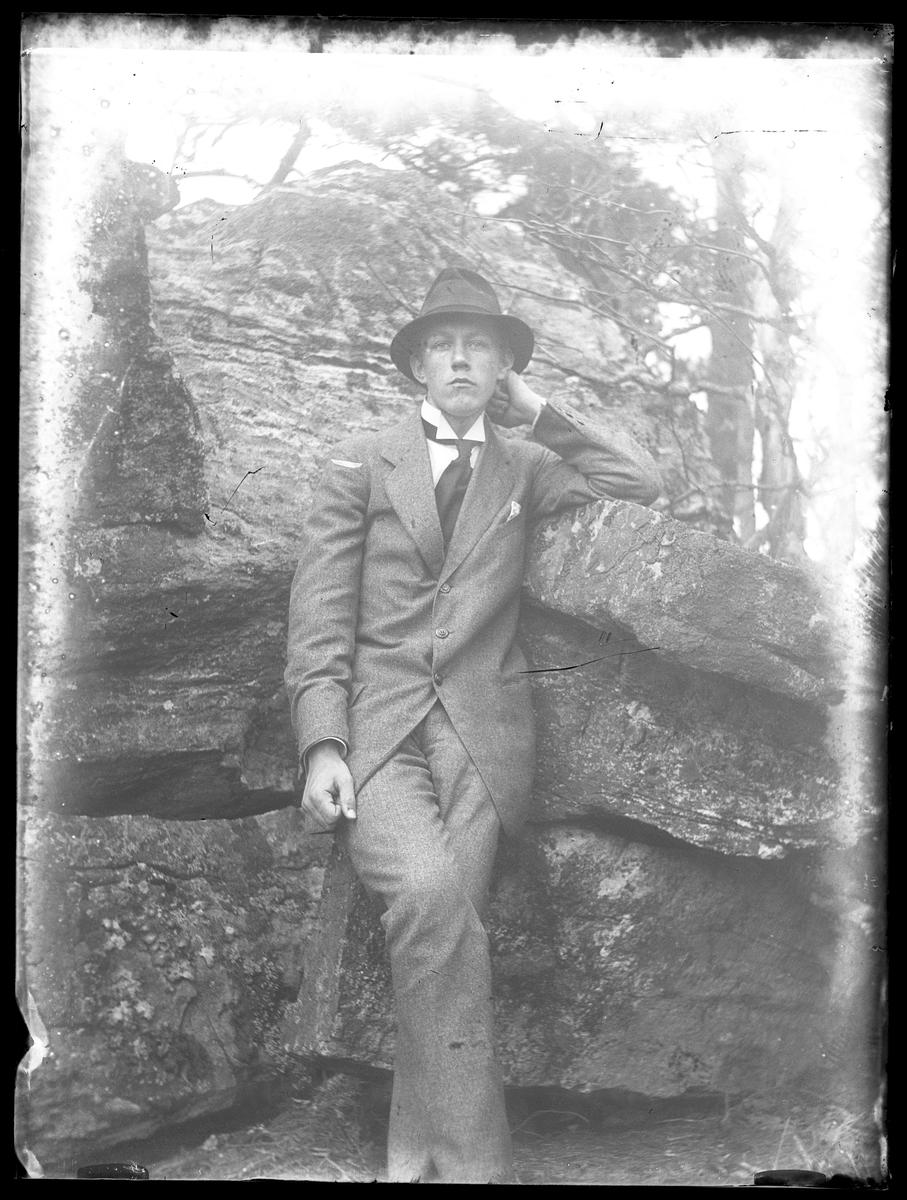 Porträtt av Gusten Hansson iklädd kostym och lutande mot en sten.