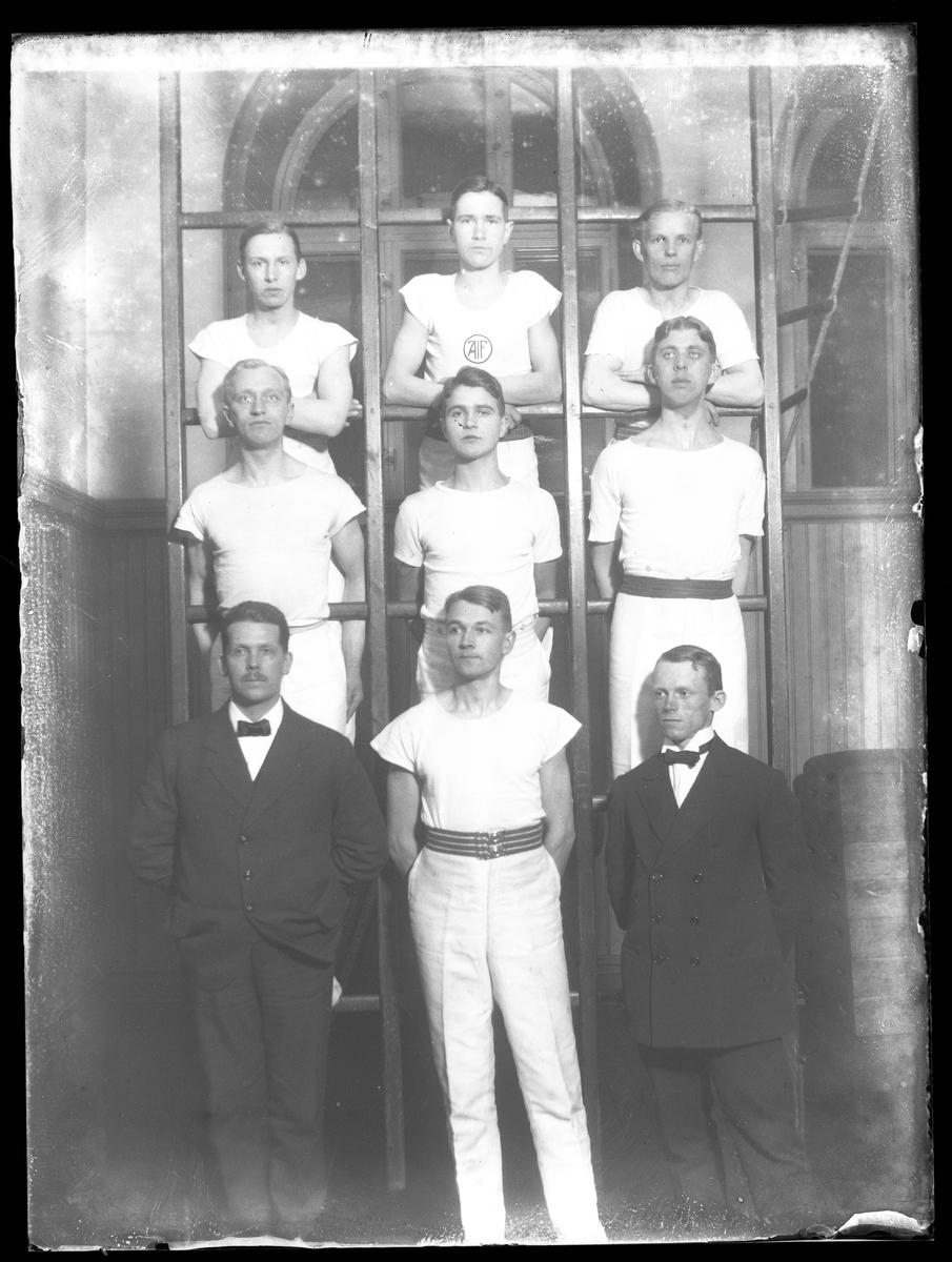 Gruppbild av gymnastiktruppen AIF (Alingsås Idrottsförening). Sex vitklädda gymnaster står uppställda i tre ribbstolar medan två kostymklädda män står på golvet framför, emellan dem står ytterligare en vitklädd gymnast.