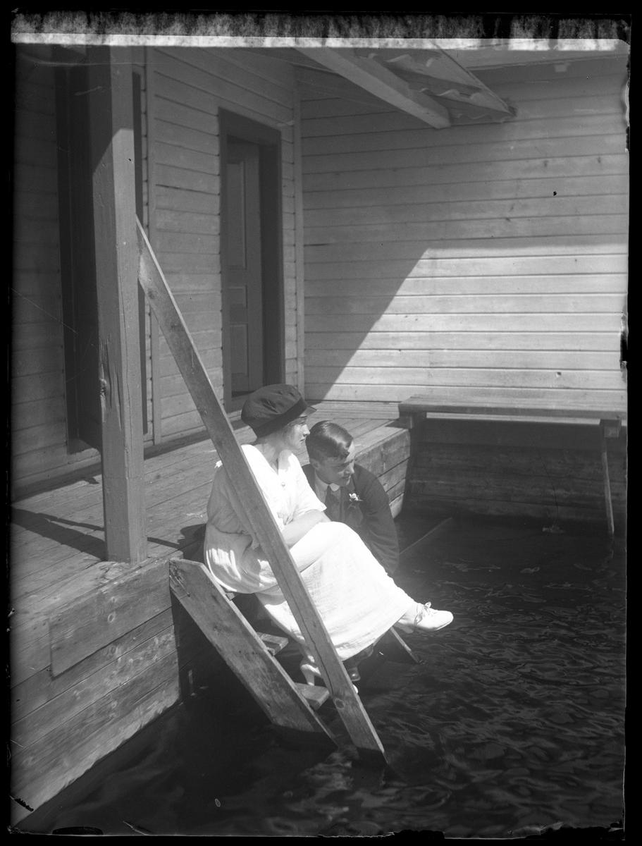 Annie Hultén, i vit klänning och keps, och Harry Andersson, i mörk kostym, sitter på ett av stegen till en badstege.