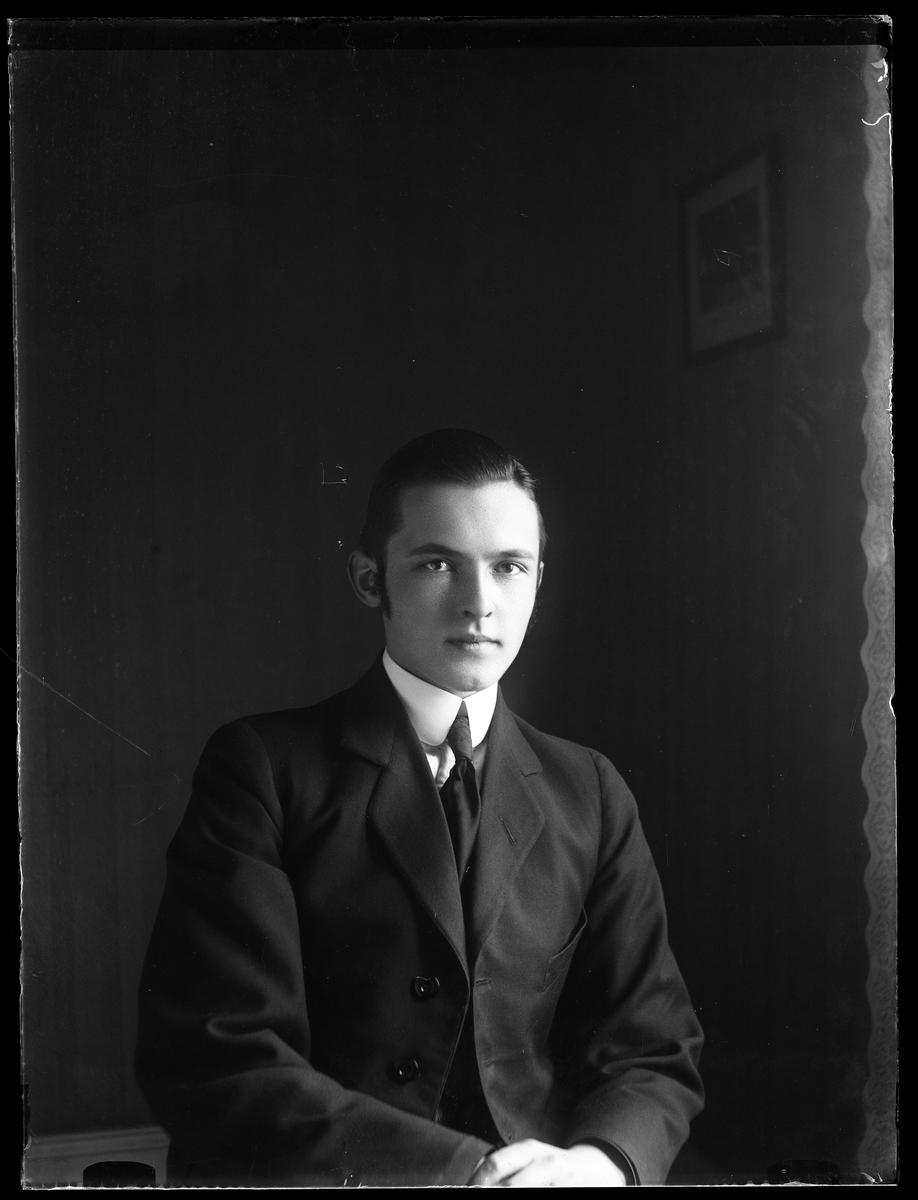 Porträtt av Folke Olsson i mörk kostym, skjorta och slips.