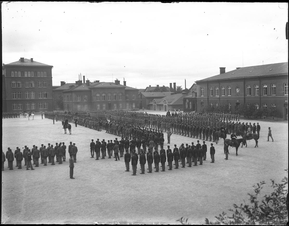 Uniformerade militärer uppställda på gårdsplan utanför garnisonsbyggnaden. Bilden tagen under fotografen Harald Olssons excercistid.