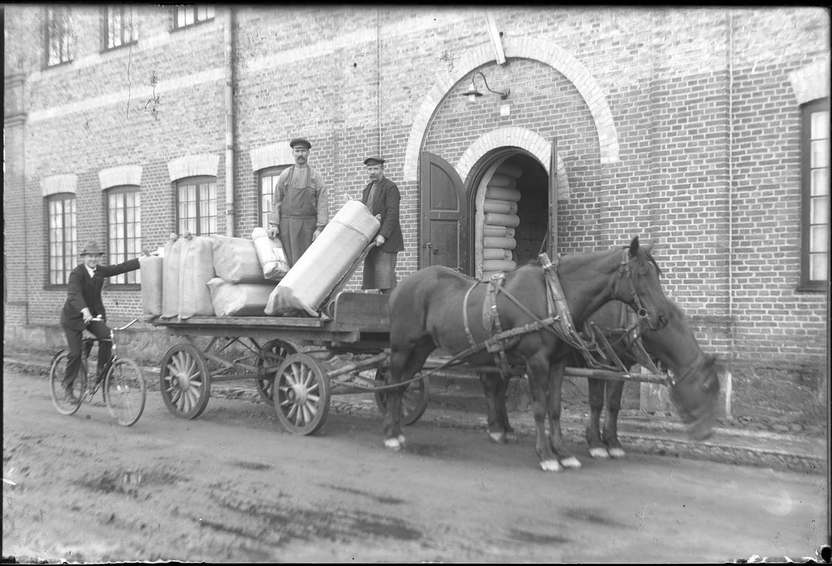 Alingsås bomullsväveris drängar lastar textilbalar på en kärra som spänts för två hästar. Bredvid sitter en man på en cykel.