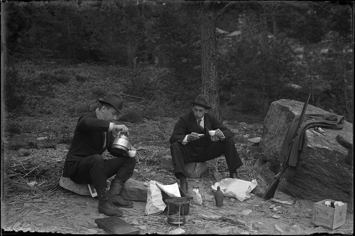 Hugo Larsson och Harald Olsson tar en fikapaus under en fiske och jakttur. På bilden sitter de på varsin sten med kaffekopp i handen. Harald häller upp kaffe ur en kanna och framför dem står ett Primuskök, en påse från A. Olssons specerier mm. Ett gevär står lutad mot en stor sten och på stenen ligger en rock, en pipa, tobak och en död ekorre.