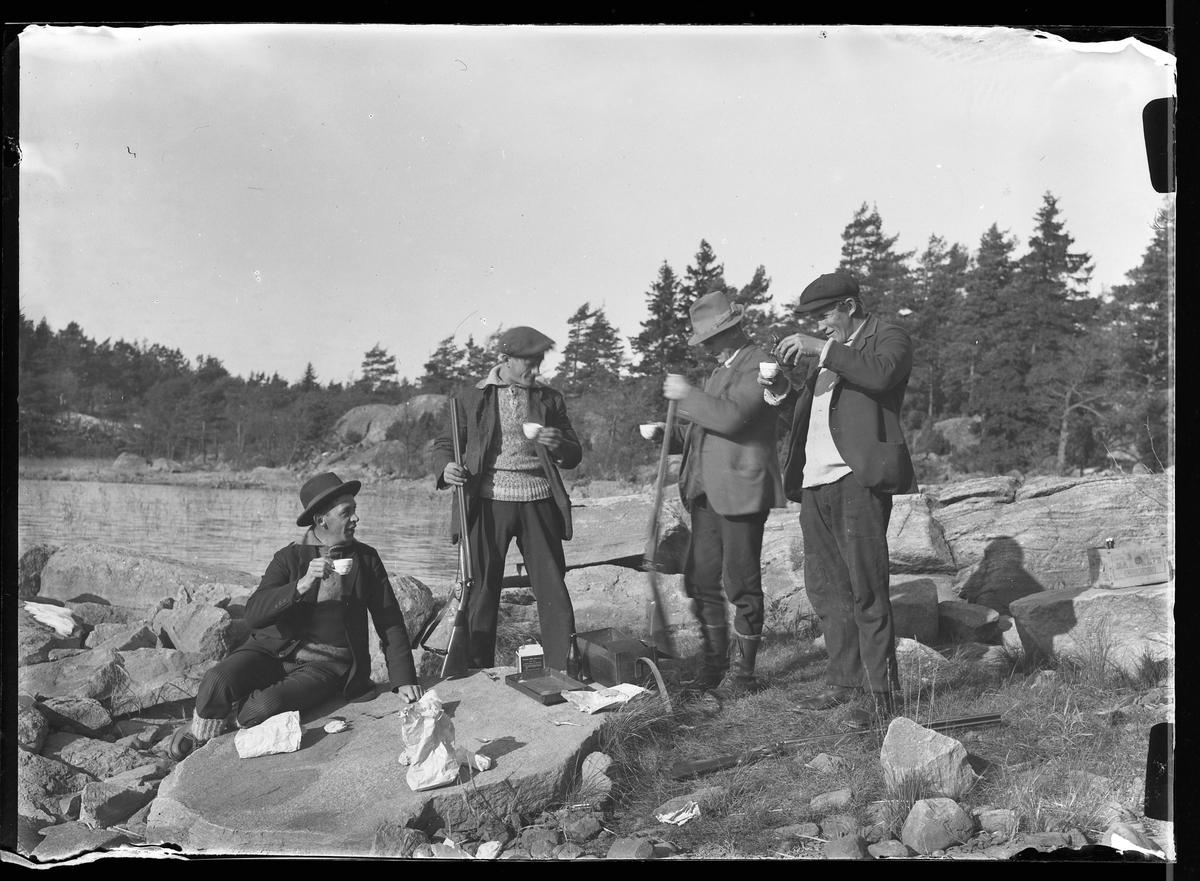 Fyra män tar kafferast under jakt på Risö. En av dem sitter ner på en sten medan de andra står bredvid. Framför dem syns bland annat smörgåspaket och en unica-box.