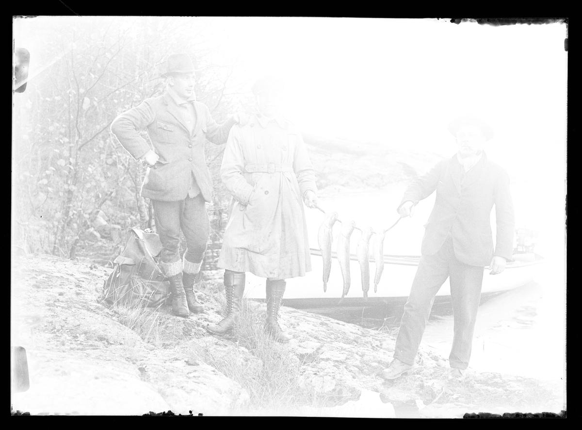 Överexponerat fotografi av Gustaf Claesson och Hjelm (möjligen John Hjelm) som håller upp fyra fiskar som de fångat. Bredvid står Harald Olsson och i bakgrunden syns en båt uppdragen på klipprona.