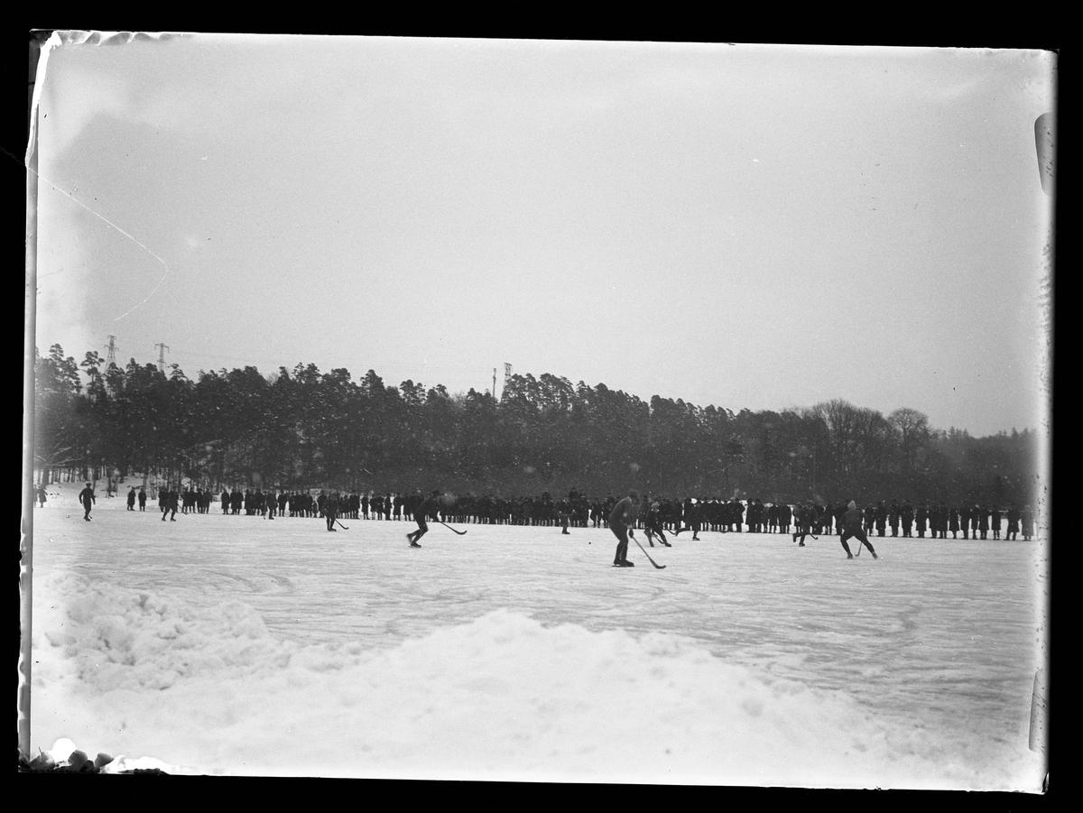 Ett antal personer spelar bandy på isen medan en grupp människor står bredvid och tittar på.
