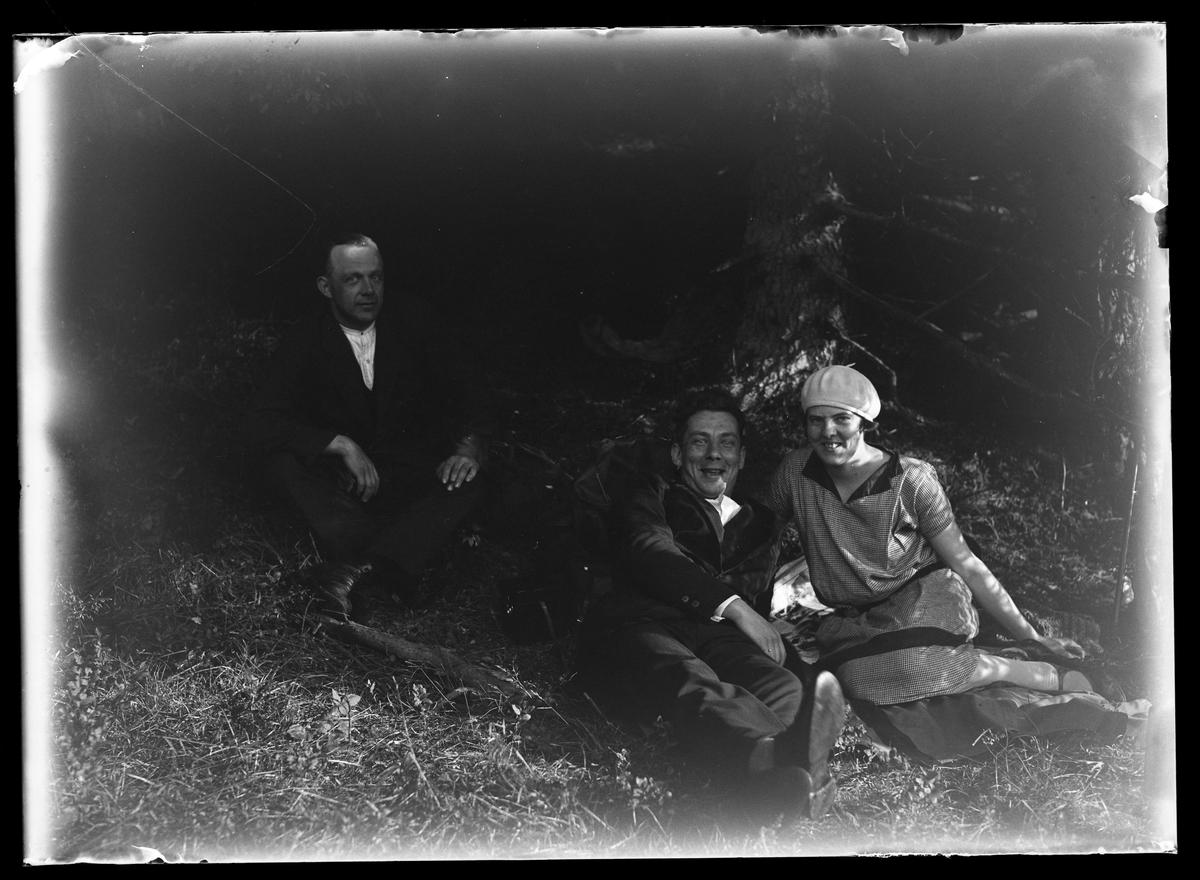 """Två män och en kvinna ligger i gräset vid en gran. Tolkat som Lizzie Skoglund och Harald Olsson längst fram. Mannen i bakgrunden är okänd. I fotografens egna anteckningar står det: """"3 plåtar från Floda""""."""