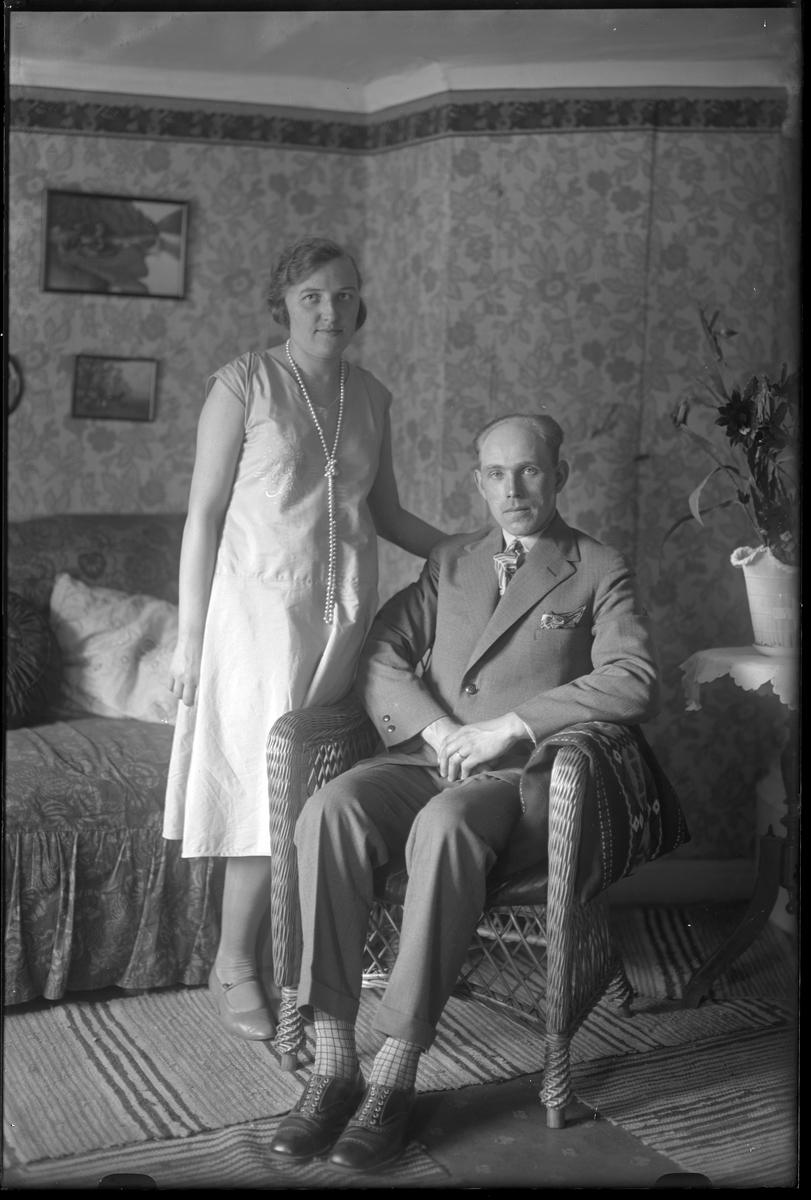 """En kvinna står vid sidan om en korgstol där det sitter en man. I fotografens egna anteckningar står det """"Fröken Andersson (Ståhl)""""."""
