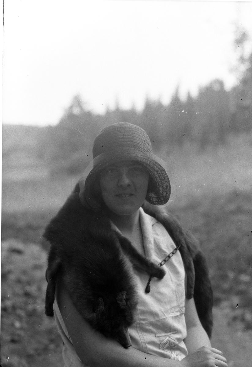 Porträtt av Lizzie Skoglund med en rävboa om axlarna och stråhatt.